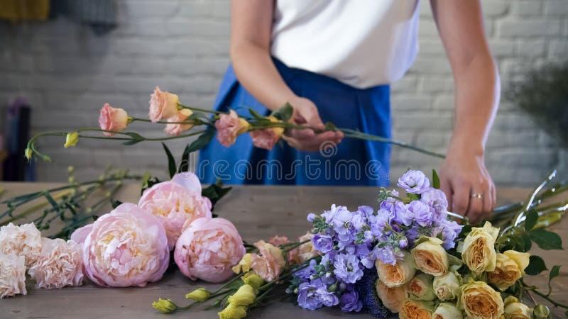 Kvinna som skapar blommasammansättningar i konststudio royaltyfri bild