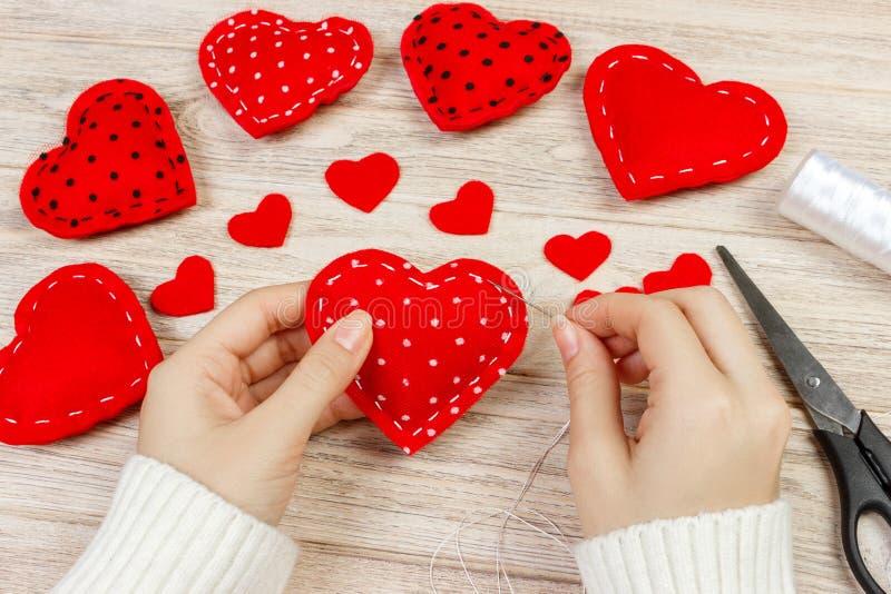 Kvinna som skapar röd hjärta på trätabellen gåva för den handgjorda dagen för St-valentin` s arkivfoto