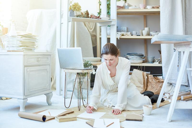 Kvinna som skissar i studio arkivfoto