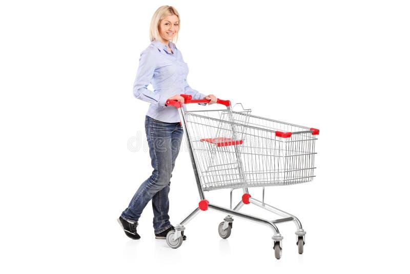 Kvinna som skjuter en shoppingspårvagn royaltyfri bild