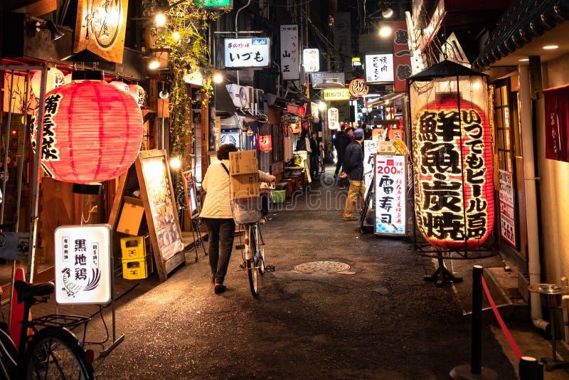 Kvinna som skjuter hennes gata för gränd för arbetscykel tillbaka i Namba, Japan royaltyfri foto