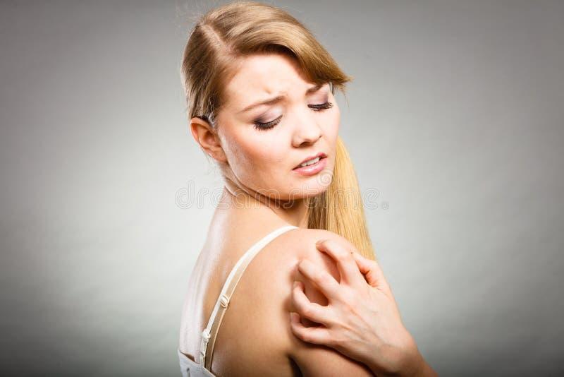Kvinna som skrapar hennes kliande arm med den överilade allergin arkivbilder