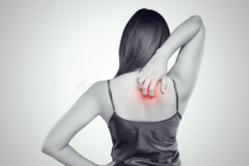 kvinna som skrapar hennes kliande baksida med den överilade allergin royaltyfri bild