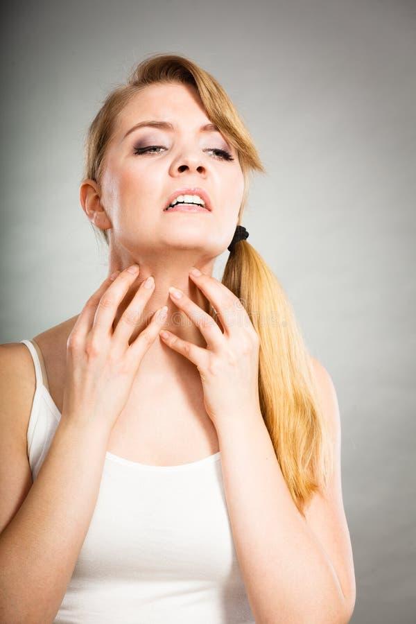 Kvinna som skrapar hennes kliande hals med den överilade allergin arkivbild