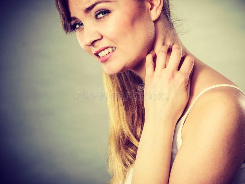 Kvinna som skrapar hennes kliande hals med den överilade allergin royaltyfri fotografi