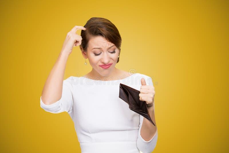 Kvinna som skrapar i huvud och inom ser av den tomma plånboken som har inga pengar royaltyfria foton