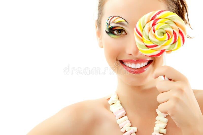 Kvinna som skrattar med den attraktiva godisen och härligt sminkbarn royaltyfri bild