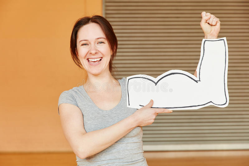 Kvinna som skrattar och visar falska muskler royaltyfri bild