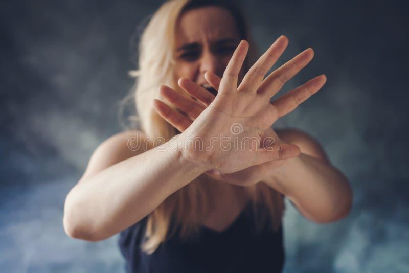 Kvinna som skriker i skräck som försvarar sig med händer royaltyfria bilder