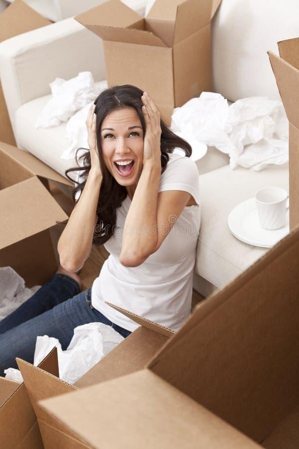 Kvinna som skriker packa upp askar som flyttar huset royaltyfri foto