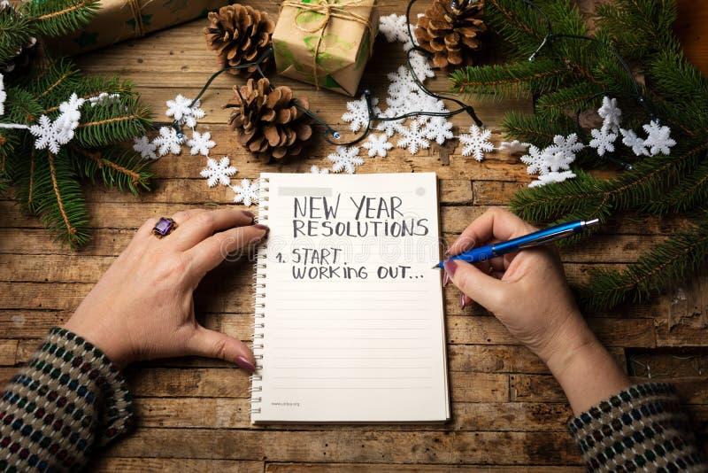 Kvinna som skriver upplösningslistan för nytt år royaltyfria foton