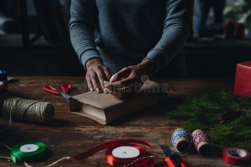 Kvinna som slår in boken som julgåvan royaltyfria foton