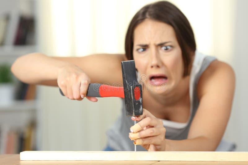 Kvinna som slår fingret med en hammare royaltyfria bilder