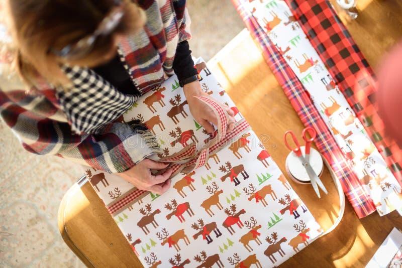 Kvinna som slår in julklappar på tabellen i hem- hög vinkel fotografering för bildbyråer