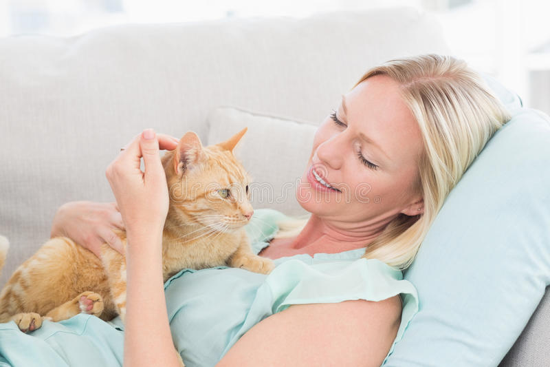 Kvinna som slår katten, medan ligga på soffan royaltyfri bild