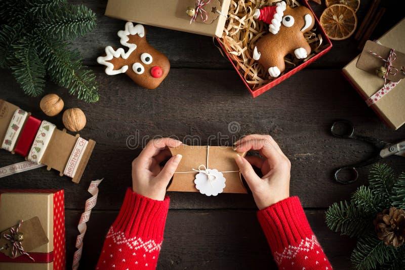 Kvinna som slår in moderna julklappar med den tomma gåvaetiketten på gammal träbakgrund Ögonfågelsikt royaltyfri foto