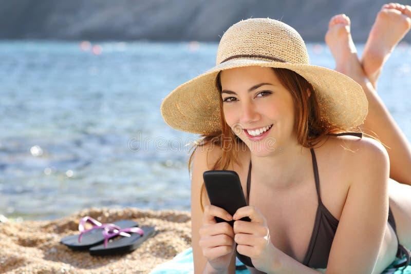 Kvinna som smsar i en smart telefon på ferier på stranden arkivfoton