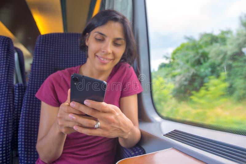 Kvinna som smsar på hennes telefon under hennes tur i drev arkivfoto