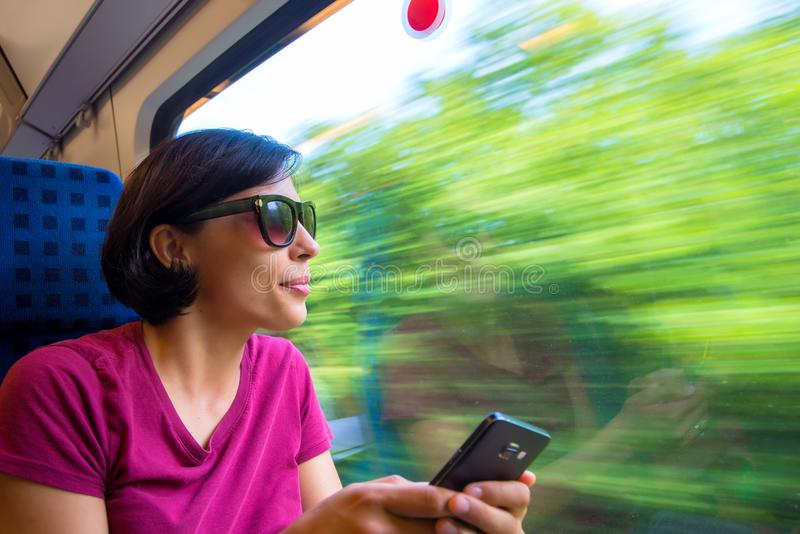 Kvinna som smsar på hennes telefon under hennes tur i drev royaltyfria bilder