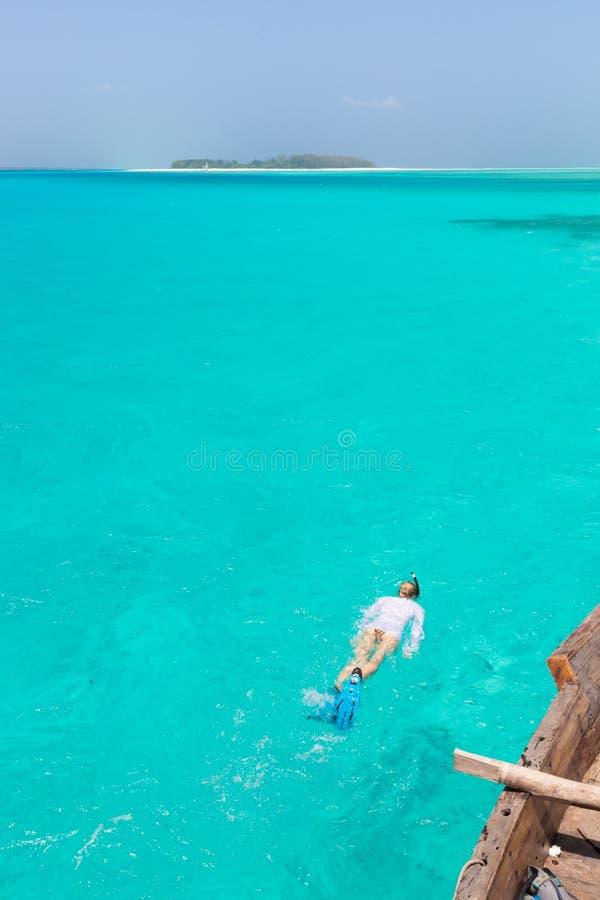 Kvinna som snorklar i det klara grunda havet av den tropiska lagun med turkosblått vatten arkivfoton