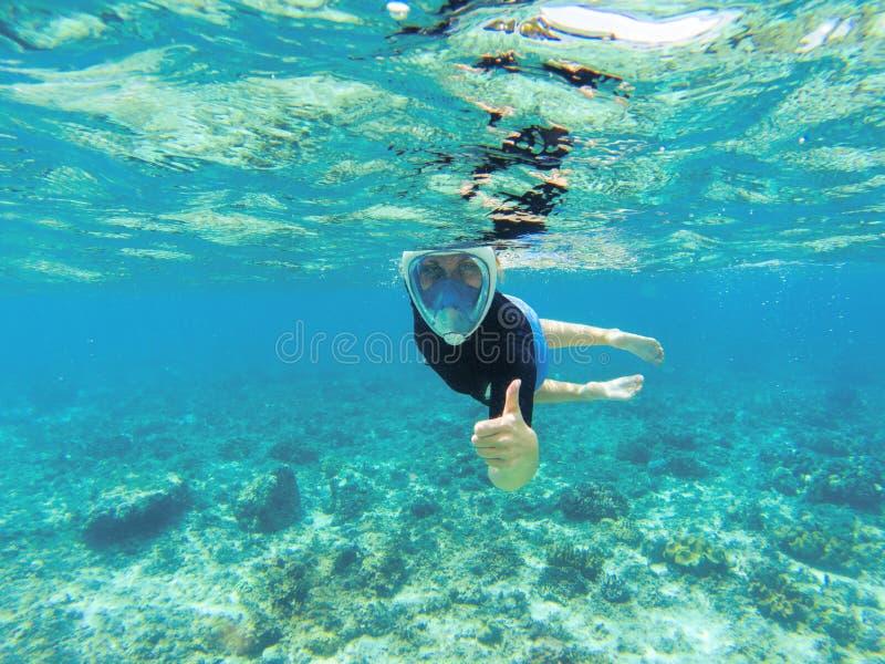 Kvinna som snorklar i klart havsvatten Snorkeln visar tummen den oavkortade framsidamaskeringen arkivfoton