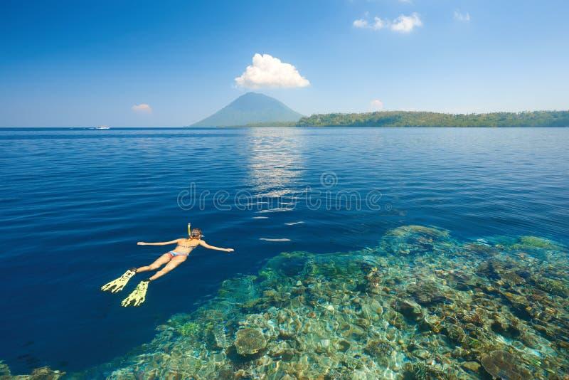 Kvinna som snorklar i klart tropiskt vatten på en bakgrund av isl royaltyfri fotografi