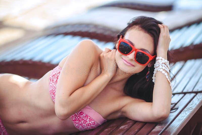 Kvinna som solbadar i bikini på den tropiska loppsemesterorten. Härlig ung kvinna som ligger på near pöl för soldagdrivare. royaltyfri fotografi