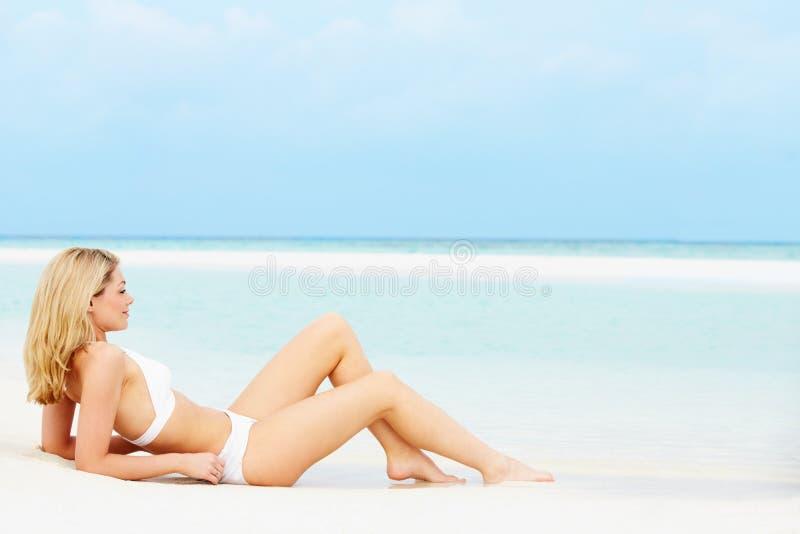 Kvinna som solbadar på härlig strandferie arkivfoto