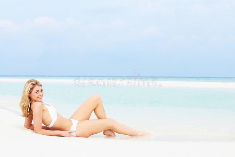 Kvinna som solbadar på härlig strandferie arkivbild