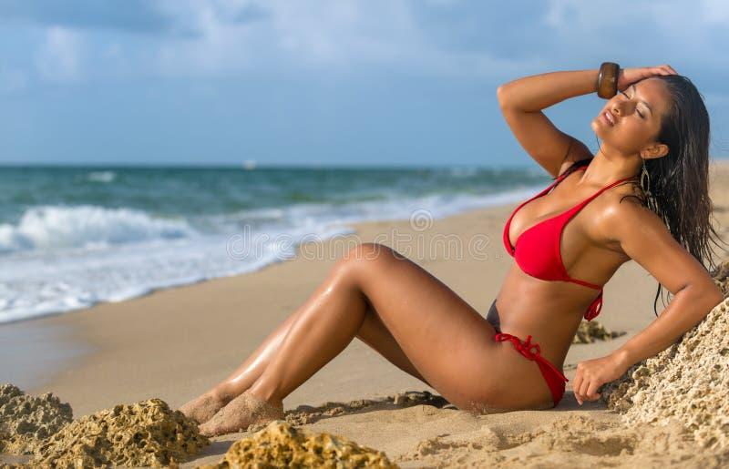 Kvinna som solbadar på stranden arkivbild