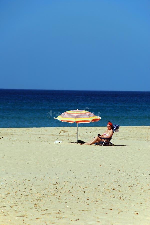 Kvinna som solbadar på stranden, Zahara de los Atunes, Spanien fotografering för bildbyråer
