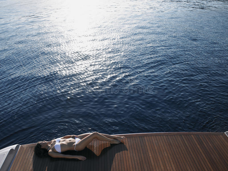 Kvinna som solbadar på yachts golvtilja vid havet arkivfoto
