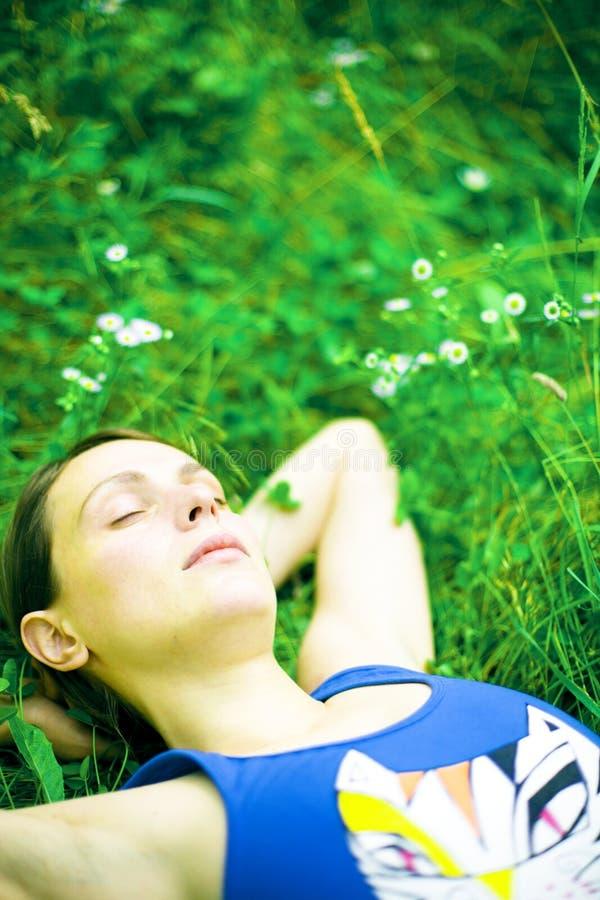Kvinna som sovar på grönt gräs royaltyfri fotografi
