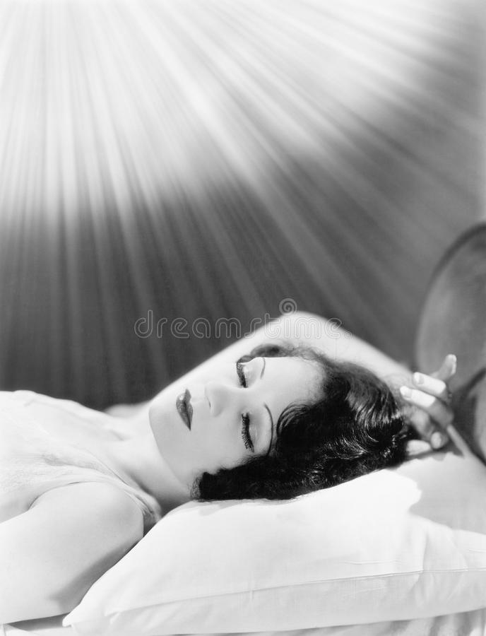 Kvinna som sover i en säng med strålar av ljus som skiner på henne (alla visade personer inte är längre uppehälle, och inget gods royaltyfri fotografi