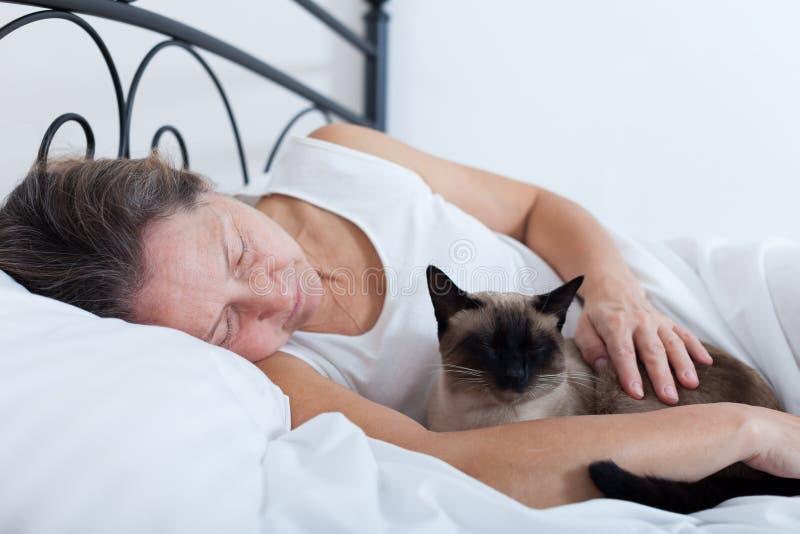 Kvinna som sover i omfamning med katten royaltyfria bilder
