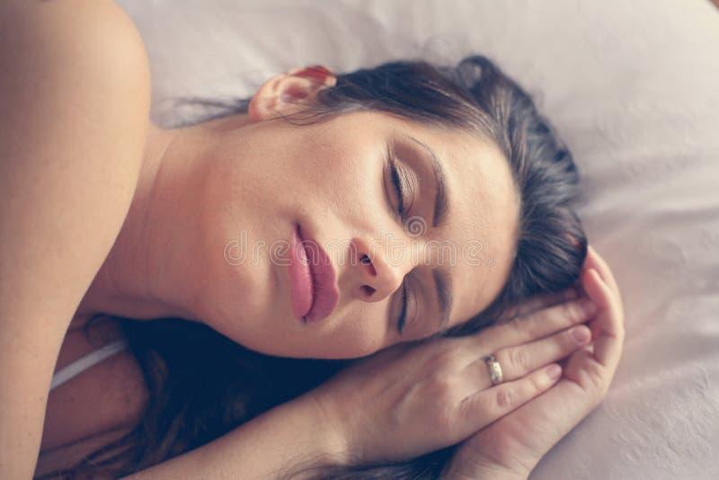Kvinna som sover i säng bara royaltyfri bild