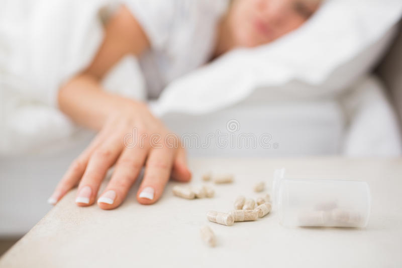 Kvinna som sover i säng med preventivpillerar i förgrund royaltyfria foton