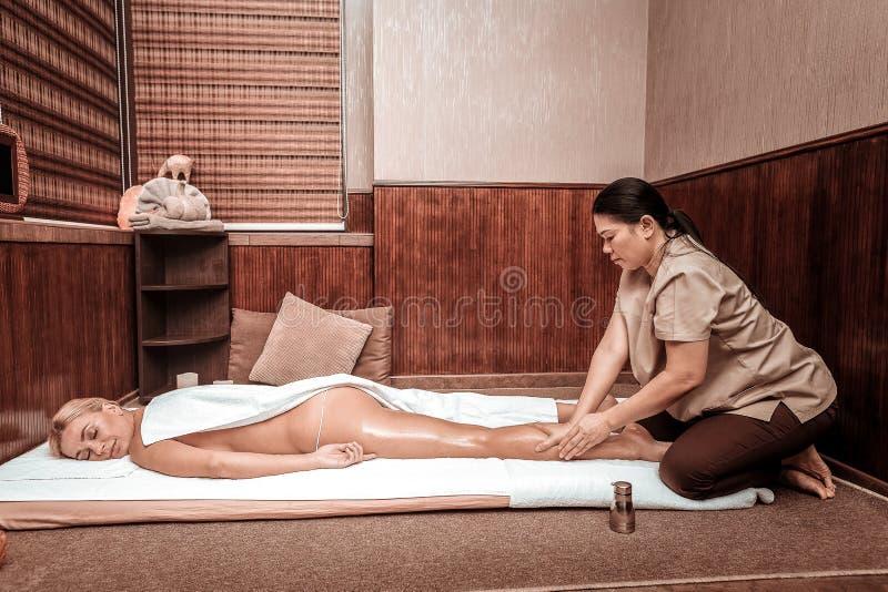 Kvinna som sover nästan under hennes oljamassage royaltyfri fotografi
