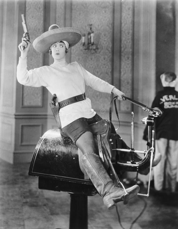 Kvinna som spelar cowgirlen på mekanisk häst arkivbilder