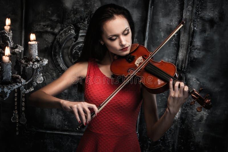 Kvinna som spelar fiolen i mystikerinre arkivfoto