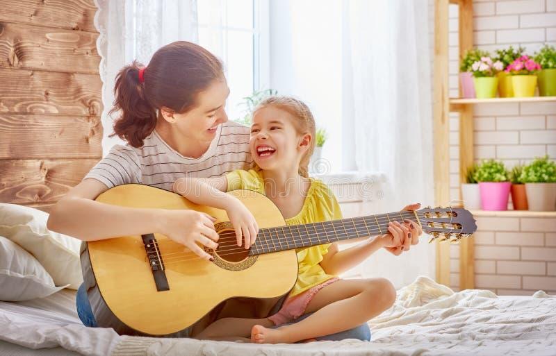 Kvinna som spelar gitarren för barnflicka arkivfoto