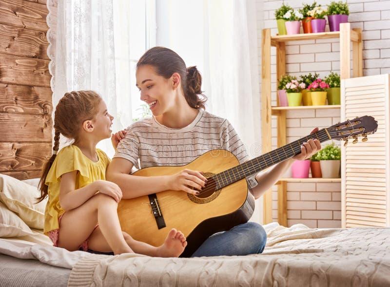 Kvinna som spelar gitarren för barnflicka royaltyfria bilder