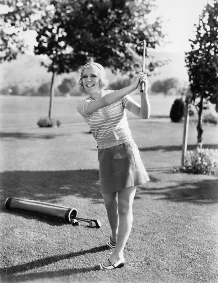 Kvinna som spelar golf på en golfbana (alla visade personer inte är längre uppehälle, och inget gods finns Leverantörgarantier so royaltyfri bild