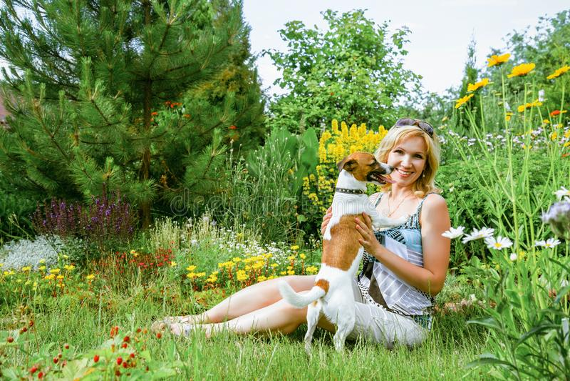 Kvinna som spelar med en hund arkivfoto
