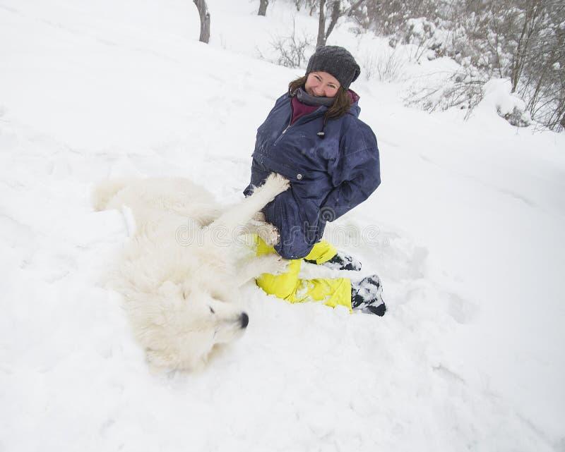 Kvinna som spelar med en vit hund i snön arkivbild