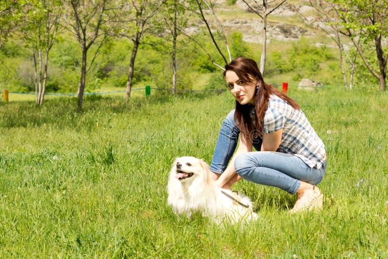 Kvinna som spelar med hennes hund i gräs arkivbilder