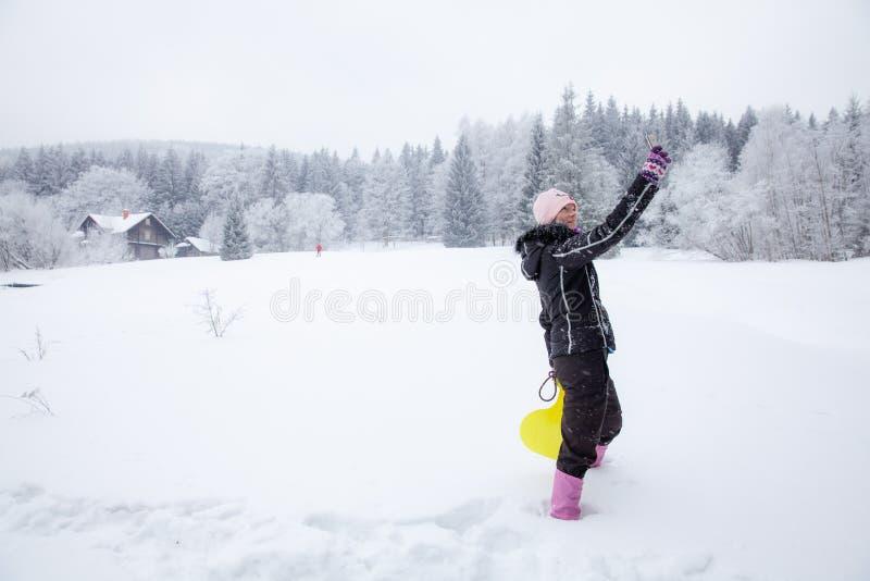 Kvinna som spelar med hennes hund p? insn?ad vinter ta bilder vid telefonselfie royaltyfria foton