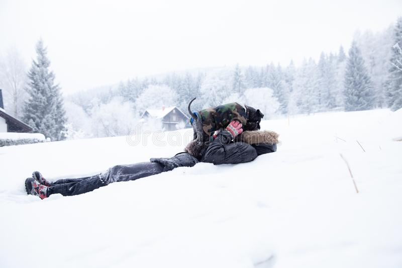 Kvinna som spelar med hennes hund p? insn?ad vinter ta bilder vid telefonselfie fotografering för bildbyråer