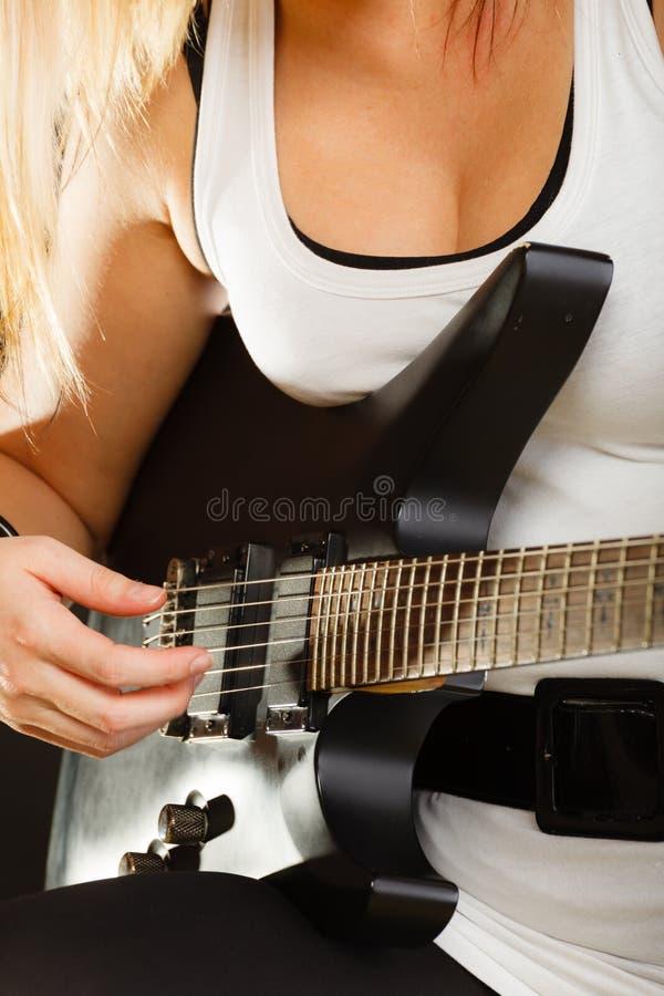 Kvinna som spelar på den elektriska gitarren, svart bakgrund royaltyfria foton