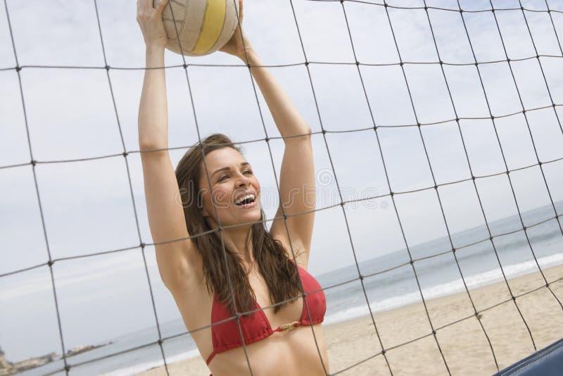 Kvinna som spelar salvabollen på stranden arkivfoto